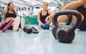 image of health center  - Closeup of black iron kettlebell and people group sitting on the floor of a fitness center in the background - JPG