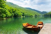 stock photo of pier a lake  - Wooden boats at pier on mountain lake - JPG