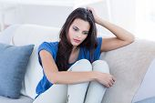 pic of thoughtfulness  - Thoughtful beautiful brunette sitting on the couch in the living room - JPG