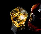 picture of whiskey  - top of view of whiskey with ice in glass on black background with reflection - JPG