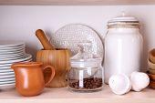 stock photo of kitchen utensils  - Kitchen utensils and tableware on wooden shelf - JPG