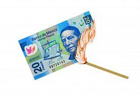 stock photo of pesos  - Twenty peso bill being burned by a lid match - JPG