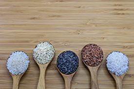 picture of rice  - Variety of rice in wood spoon on wood background - JPG