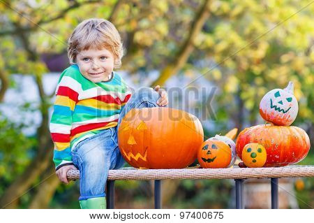 Little Kid Boy Making Jack-o-lantern For Halloween In Autumn Gar