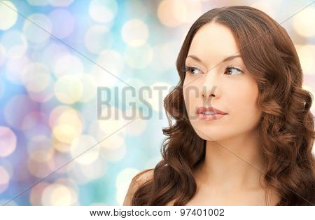 beauty, people and health concept - beautiful young woman face over blue holidays lights background