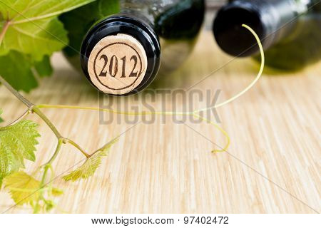 Wine Bottle With Vine And Wine Cork Put On The Board.