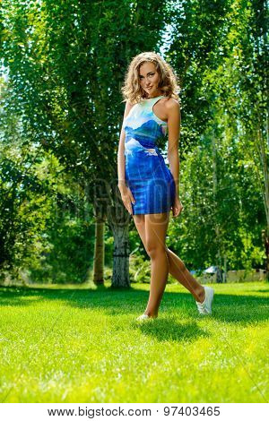 Full length portrait of a happy beautiful girl in bright summer dress walking in the summer park. Beauty, fashion. Holidays.