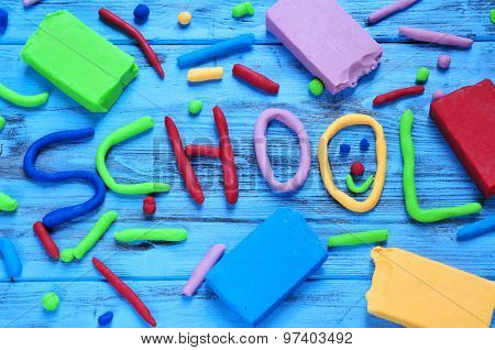 the word school written with modelling clay of different colors on a blue rustic wooden background