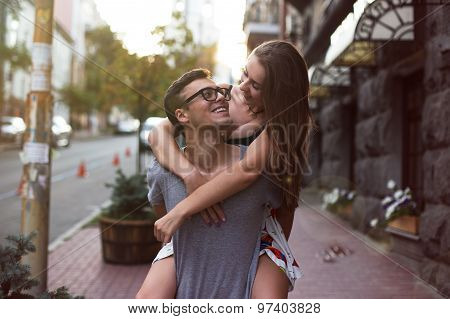 Girl riding a guy in the street of a large city beautiful. They look at each other