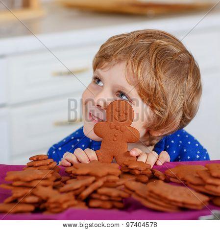 Little Boy Baking Gingerbread Cookies In Domestic Kitchen