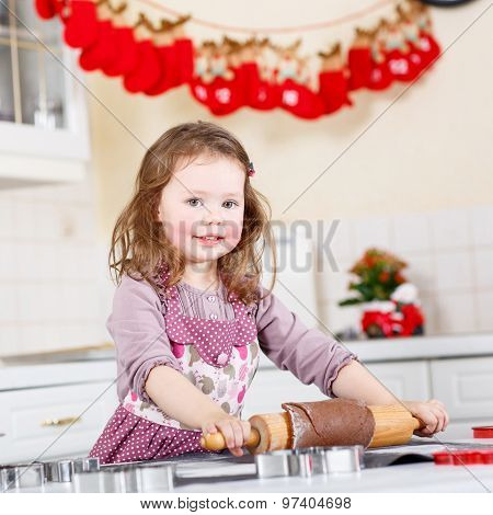 Little Girl Baking Gingerbread Cookies In Domestic Kitchen