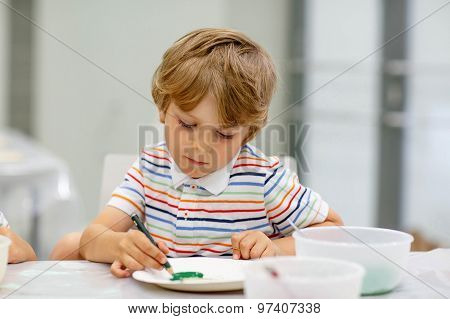 Little Blond Boy Mixing Different Colors And Painting