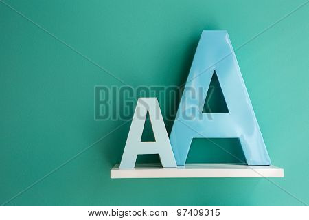 Letters A small and big size turquoise color on a white shelf.