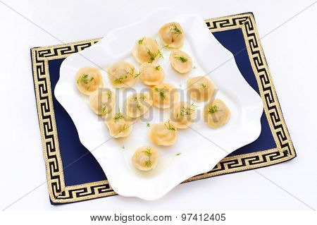 Traditional dumplings with filling and greens on white plate