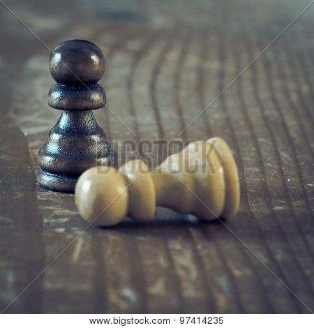 Two Chess Pieces On Wooden Table.