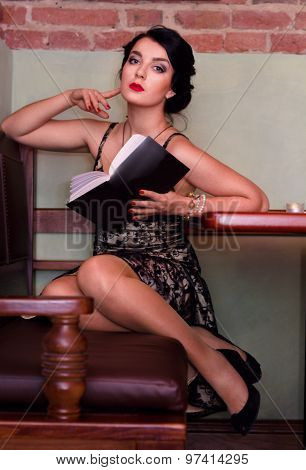Beautiful Sexy Young Woman Sitting At The Cafe Table With A Book.