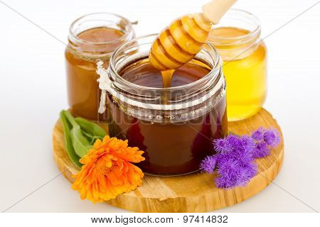 Glass Jar Of Fresh Honey With Drizzler And Flowers Isolated On White Background