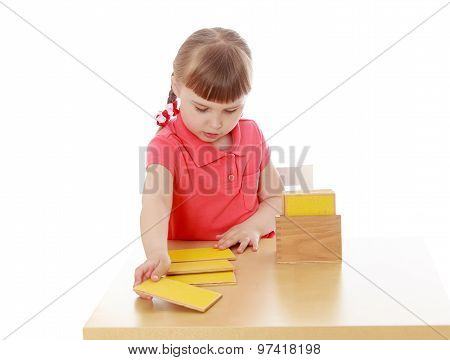 little girl working at the table Montessori kindergarten