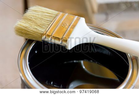 Brush in bank  with black paint