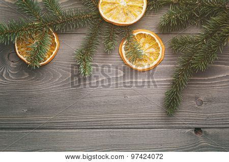 spruce twig with dried orange slices on old table, vintage photo