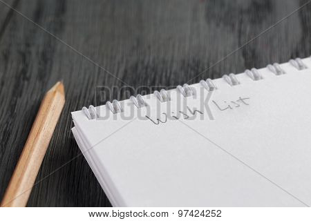 closeup photo of open empty notepad with wish list phrase