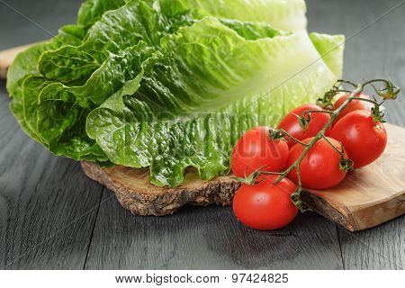 fresh romain green salad and tomatoes on olive board