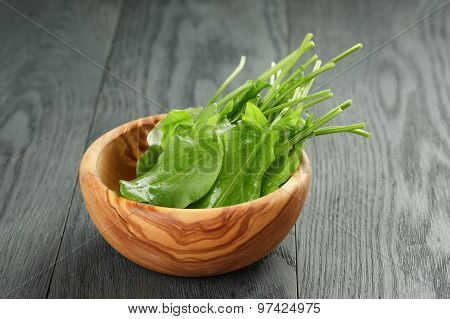 fresh sorrel leaves in olive bowl on oak wood table
