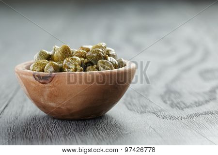 marinated capers in olive bowl on wood table with copy space