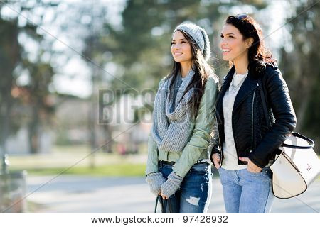 Two Young Women Taking A Walk In The Park