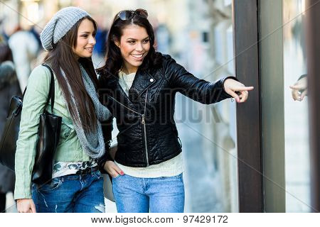 Two Young Women Pointing At A Show-window