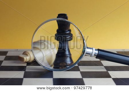 Chess Fight Concept With Two Chess Kings And Magnifying Glass.