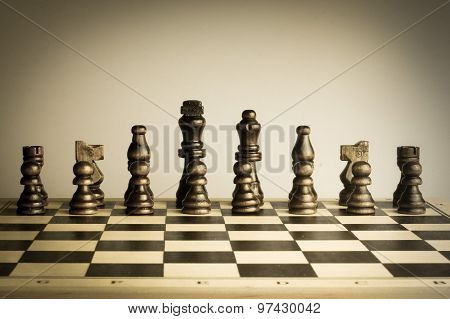 Chess pieces lined up in a row on chessboard.