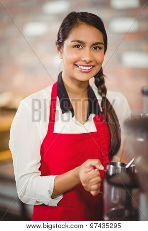 Portrait of a barista steaming milk at the coffee shop
