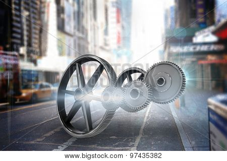 Metal cogs and wheels connecting against blurry new york street