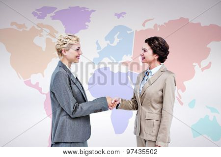 Smiling women shaking hands against grey background