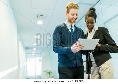 Business Partners Discussing Ideas Displayed On A Tablet On An Office Corridor