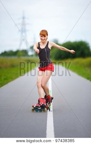 Attractive Girl Rollerblading On The Road