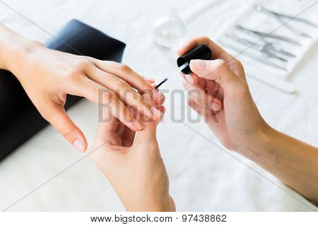 Manicurist applying cuticle softener