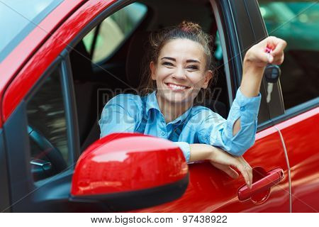 Young Cheerful Woman Sitting In A Car With Keys In Hand