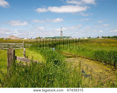 Meadow And Ditch With Industrial Construction In The Background