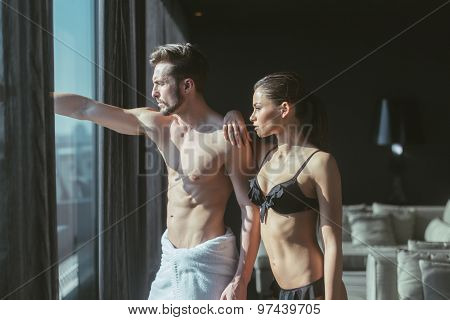 Athletic Couple In Love Looking Outside Through The Window Of A Luxurious Hotel Room