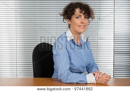 Smiling Caucasian Businesswoman Sitting In Office Looking At The Camera