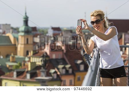 Pretty young woman taking pictures on his smartphone old european city from the observation deck.
