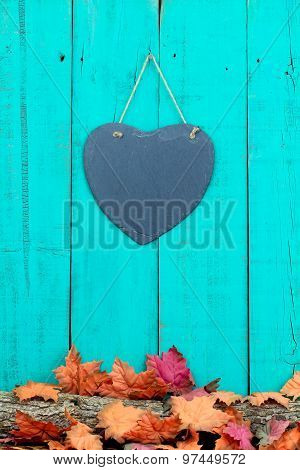 Slate heart hanging on fence with fall decor border