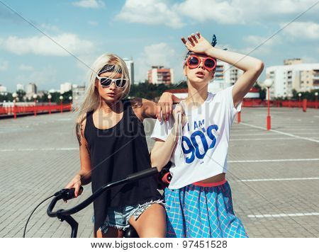 Fashion Portrait Of Attractive Young Girls With Bicycle