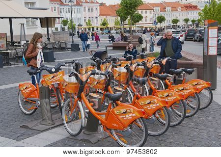 People stand at the bicycle rental point at the City Hall square in Vilnius, Lithuania.