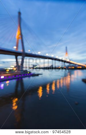 Abstract blurred bokeh light of twin suspension bridge with water reflection