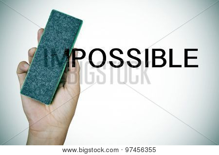 closeup of the hand of a young man deleting the word impossible with an eraser