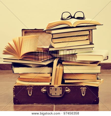 a pair of eyeglasses on a pile of books placed in an old suitcase, with a retro effect