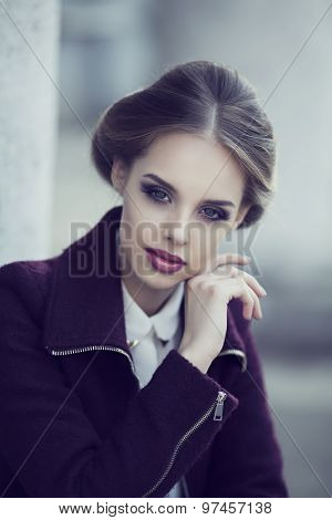 beautiful elegant woman with bright makeup wearing a warm jacket in the street